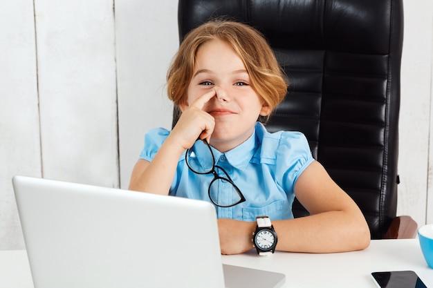 사무실에서 작업 장소에서 코를 따기 젊은 아름 다운 소녀.