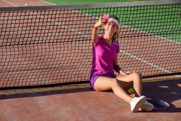 Young beautiful girl in pink uniform and sporty cap sits on a tennis court near the net and making selfie photo on smart phone at sunset. video call, communication and messaging using smart phone.