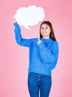 Молодая красивая девушка, указывая на белый пузырь для текста на розовом.