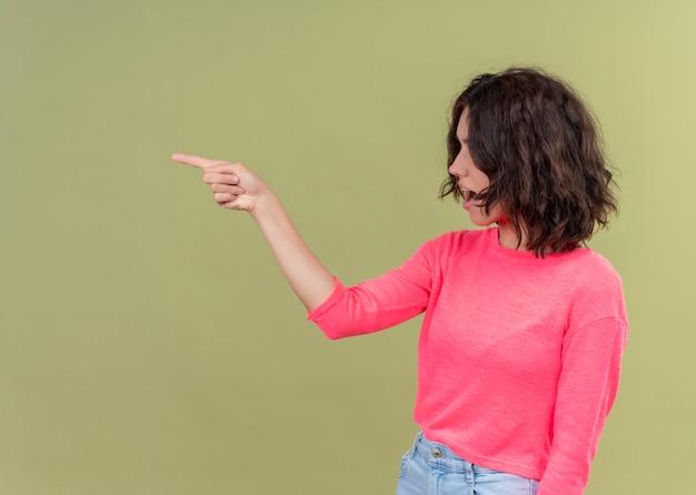 Молодая красивая девушка, указывая на левую сторону с открытым ртом, стоя в профиль на изолированном зеленом фоне