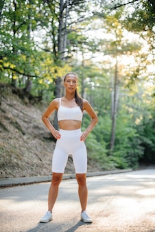 A young beautiful girl poses before running training, on the road in a dense forest, during sunset. a healthy lifestyle and running in the fresh air.