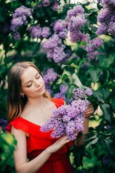 꽃 나무 사이에서 포즈를 취하는 젊은 아름 다운 소녀