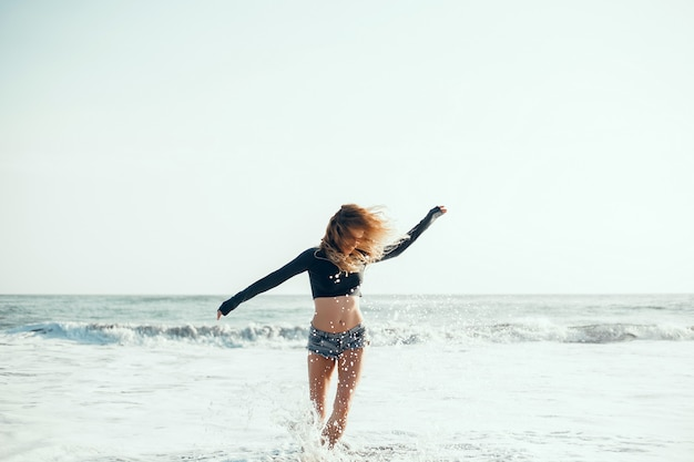 Young beautiful girl posing on the beach, ocean, waves, bright sun and tanned skin