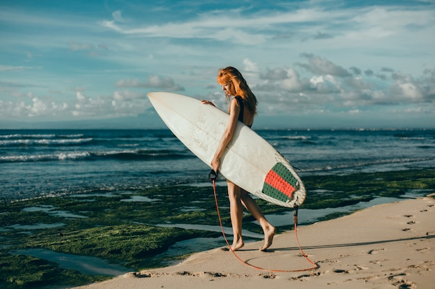 Young beautiful girl posing on the beach with a surfboard, woman surfer, ocean waves