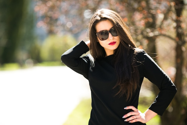 Young beautiful girl posing in a black leather jacket in the park