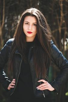 Молодая красивая девушка позирует в черной кожаной куртке в парке