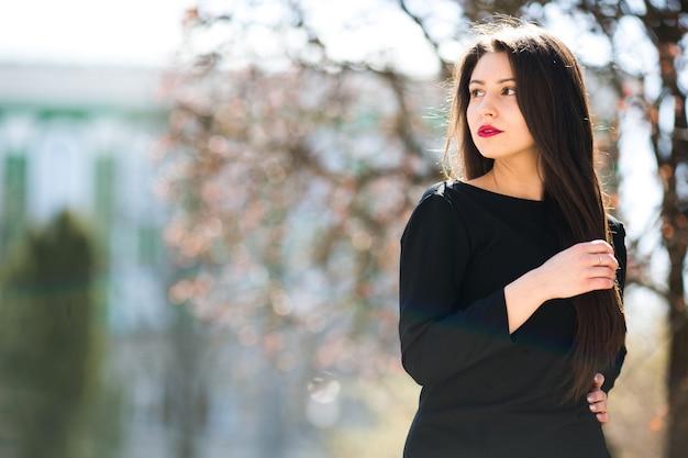 公園で黒い革のジャケットでポーズをとって若い美しい少女