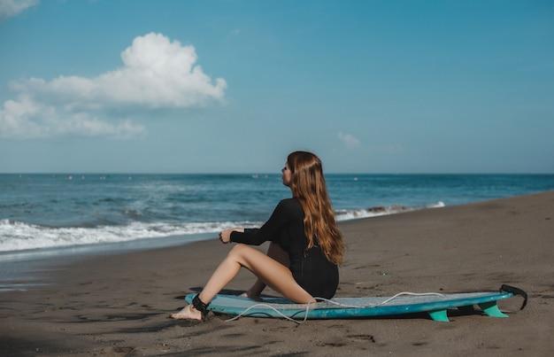 서핑 보드, 여자 서퍼, 파도와 해변에서 포즈 젊은 아름 다운 소녀