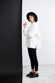 검은 색과 흰색 벽 위에 서있는 포즈를 취하는 젊은 아름 다운 소녀