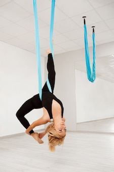 Молодая красивая девушка практикующих воздушные йоги в тренажерном зале.