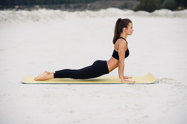 Young beautiful girl practicing yoga cobra pose on the beach at sunset. fitness sport yoga and healthy lifestyle concept.