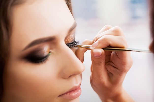 Young, beautiful girl put on make-up in a beauty salon