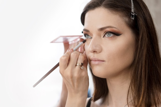 Young beautiful girl put on make-up in a beauty salon