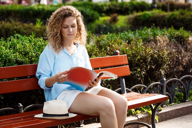 Young beautiful girl reading, sitting on bench in city park.