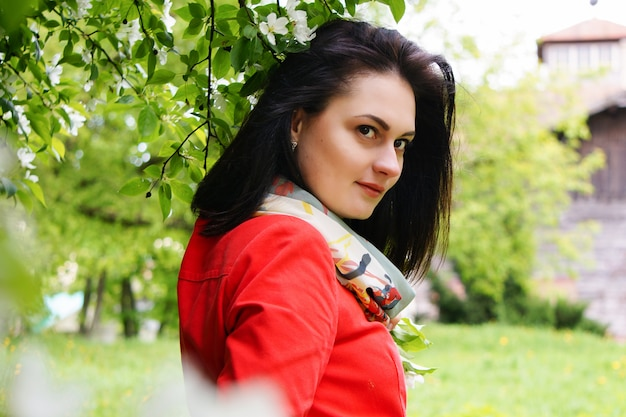 Young beautiful girl in the red coat in the park, spring,