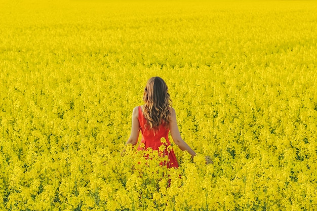 Young beautiful girl in a red dress close up in the middle of the yellow field with the radish flowers. spring season