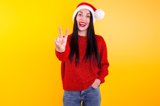 Young beautiful girl in a red santa hat. happy, smiling woman showing two fingers.