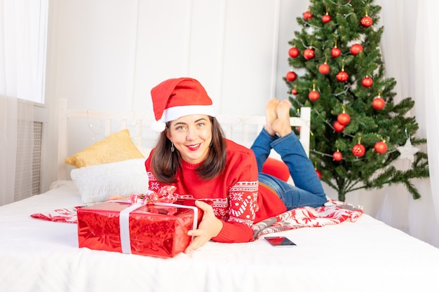 A young beautiful girl in a red sweater and hat is lying at home on the bed near the christmas tree with a big red gift