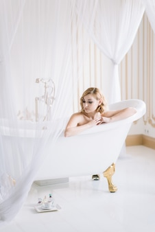 Young beautiful girl relaxes in a white bath with gold fittings in a bright room.