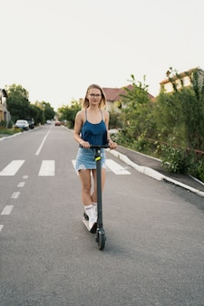 Young beautiful girl riding an electric scooter in the summer on the street