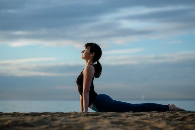 Young beautiful girl on the seashore practices yoga