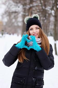 발렌타인 데이에 그녀의 손으로 마음을 보여주는 젊은 아름다운 소녀