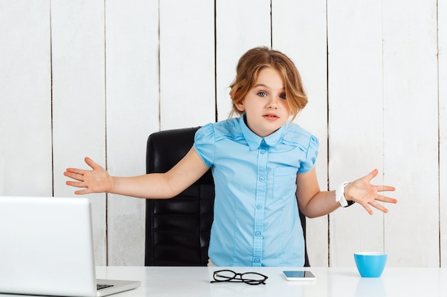 オフィスの作業場所で手をすくめ美しい少女。