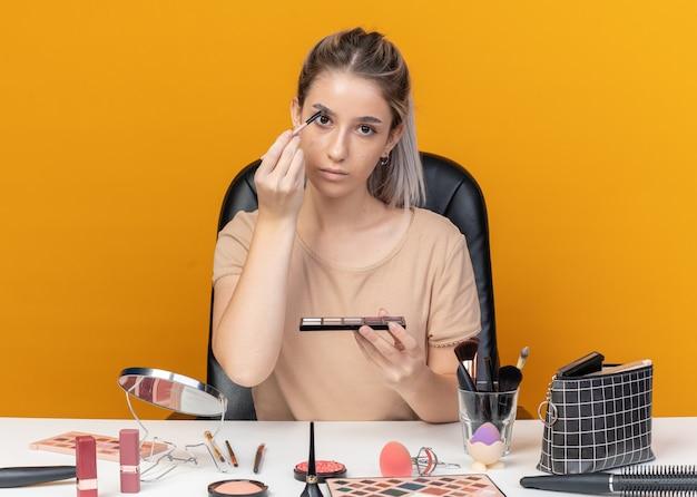 若い美しい少女は、オレンジ色の壁に分離された化粧ブラシでアイシャドウを適用する化粧ツールでテーブルに座っています。