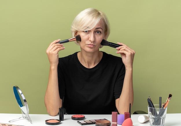 Молодая красивая девушка сидит за столом с инструментами для макияжа, нанося румяна на оливково-зеленую стену