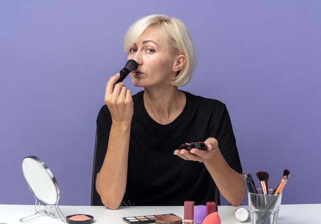 Молодая красивая девушка сидит за столом с инструментами для макияжа, нанося румяна с помощью кисти для пудры, изолированной на синей стене