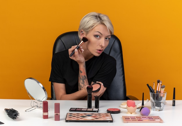 Молодая красивая девушка сидит за столом с инструментами для макияжа, нанося румяна с помощью кисти для пудры, изолированной на оранжевой стене