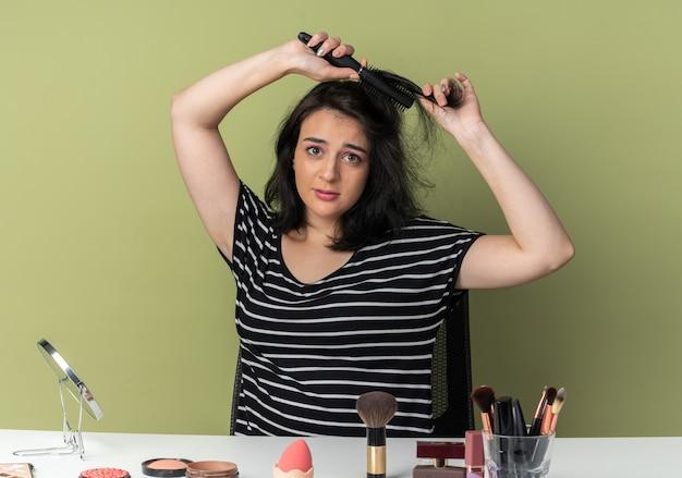 Молодая красивая девушка сидит за столом с инструментами для макияжа, расчесывая волосы, изолированные на оливково-зеленой стене