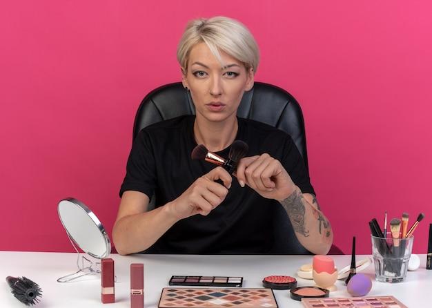 若い美しい少女は、ピンクの壁に分離されたパウダーブラシを保持し、交差する化粧ツールでテーブルに座っています。