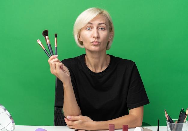 若い美しい少女は、緑の壁に分離された化粧ブラシを保持している化粧ツールでテーブルに座っています。