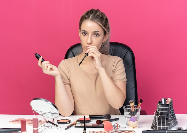 Молодая красивая девушка сидит за столом с инструментами для макияжа, держа румяна на розовой стене