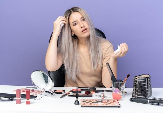 Молодая красивая девушка сидит за столом с инструментами для макияжа, нанося крем для волос на волосы, изолированные на синей стене