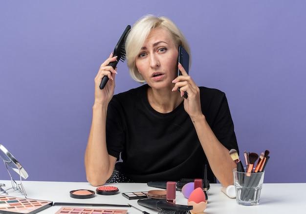 Молодая красивая девушка сидит за столом с инструментами для макияжа и разговаривает по телефону, расчесывая волосы, изолированные на синей стене