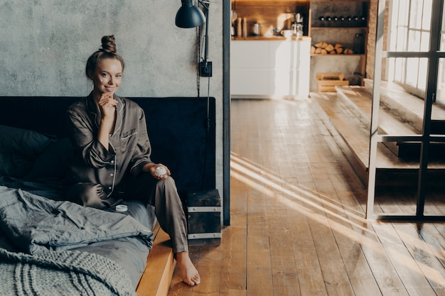 Young beautiful girl sits on bed in pajamas after waking up