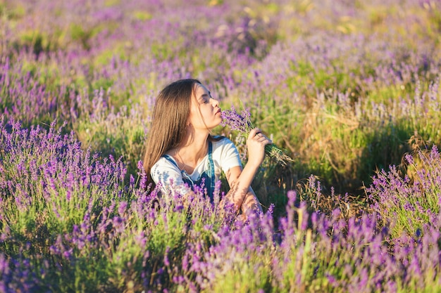 Young beautiful girl sits on a lavender meadow with a bouquet of flowers in their hands