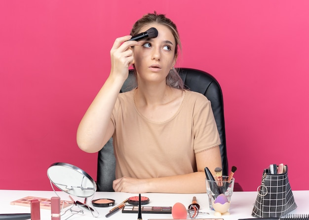 Young beautiful girl sits at table with makeup tools applying powder blush isolated on pink background