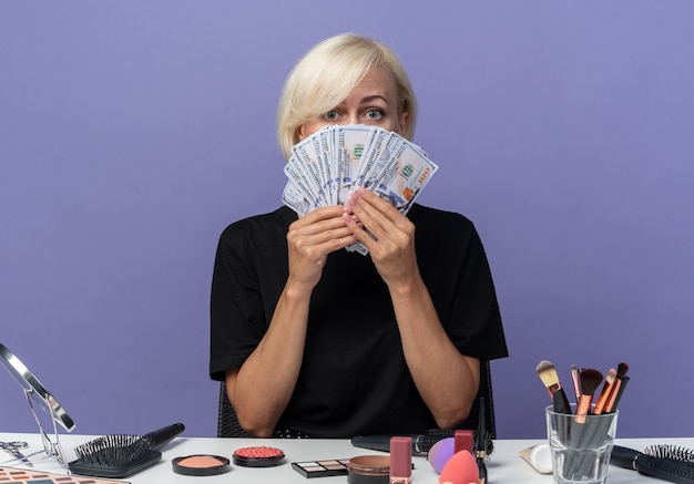 Young beautiful girl sits at table with makeup tools covered face with cash isolated on blue wall
