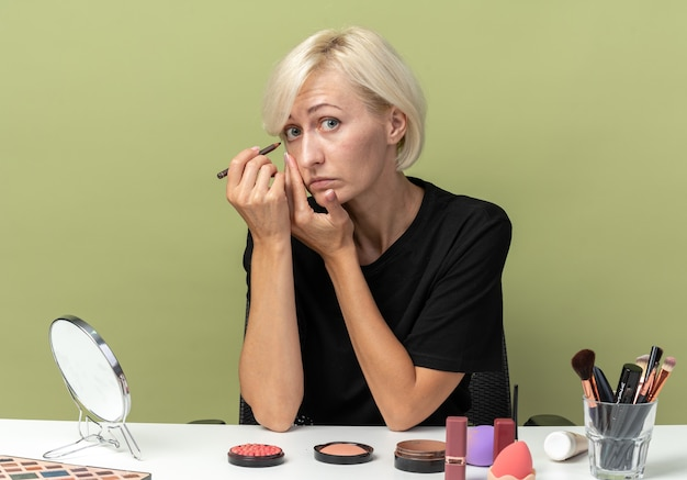 Young beautiful girl sits at table with makeup tools draw arrow with eyeliner isolated on olive green background