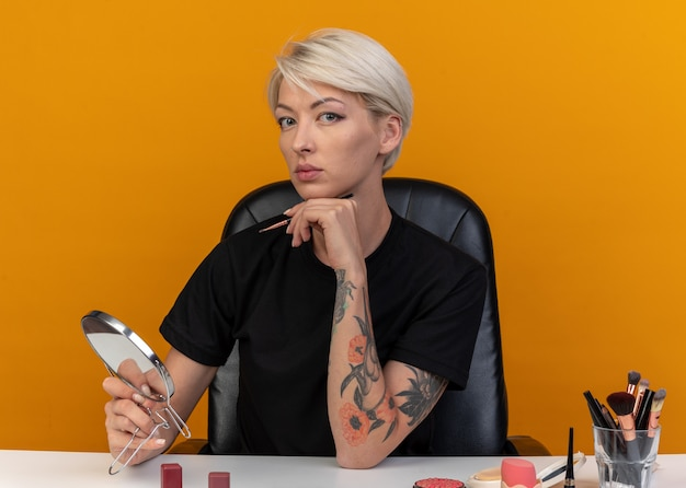 La giovane bella ragazza si siede al tavolo con gli strumenti per il trucco tenendo il pennello per il trucco con lo specchio isolato sul muro arancione