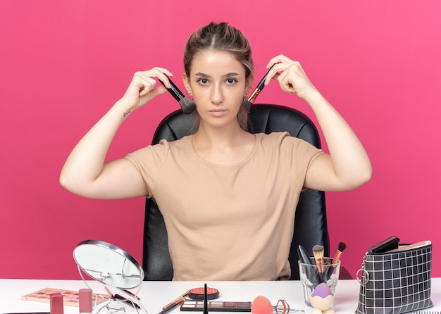 Young beautiful girl sits at table with makeup tools holding powder brush around face isolated on pink wall