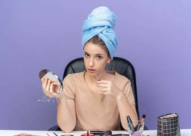 Giovane bella ragazza si siede al tavolo con strumenti per il trucco capelli avvolti in un asciugamano che tiene lo specchio applicando lucidalabbra isolato su parete blu