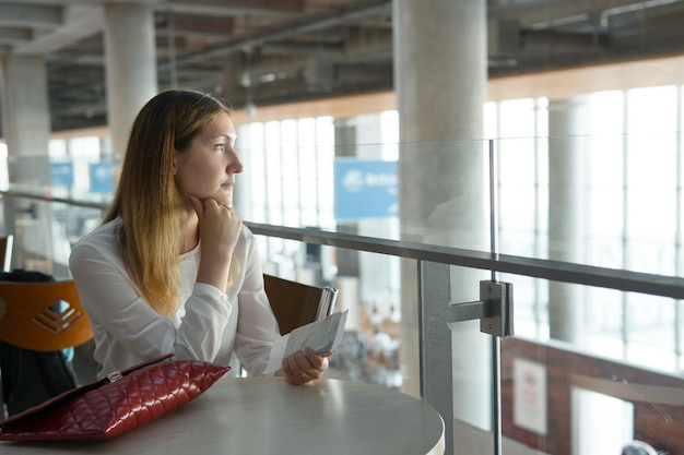 Young beautiful girl sits at table with ticket and waits for airplane