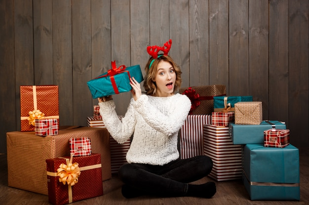 Young beautiful girl sitting among christmas gifts over wooden wall
