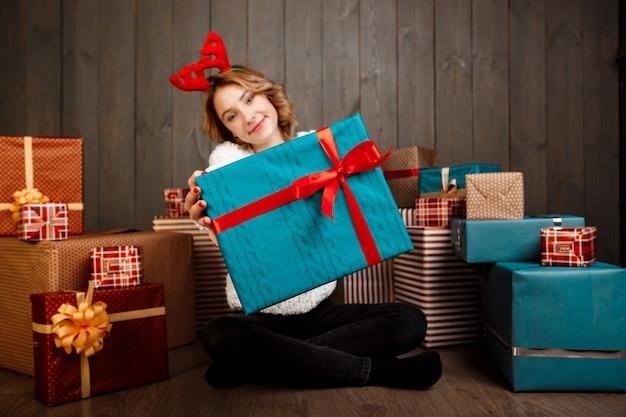 Giovane bella ragazza che si siede fra i regali di natale sopra la parete di legno