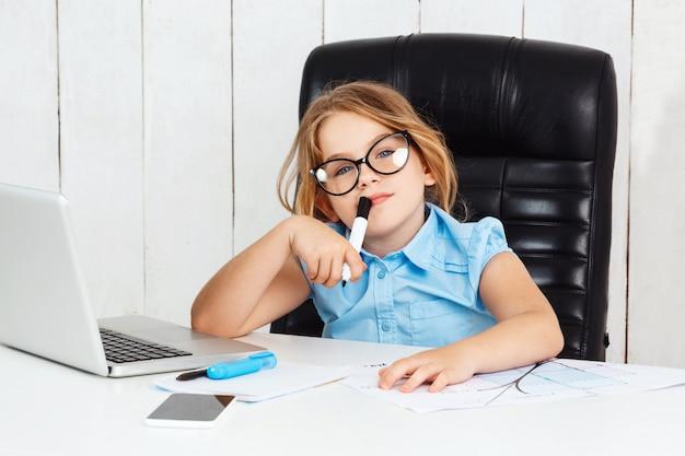 Молодая красивая девушка сидит на рабочем месте в офисе.