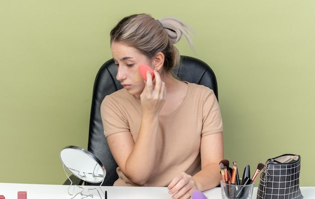 Young beautiful girl sitting at desk with makeup tools wiping tone-up cream with sponge isolated on olive green wall